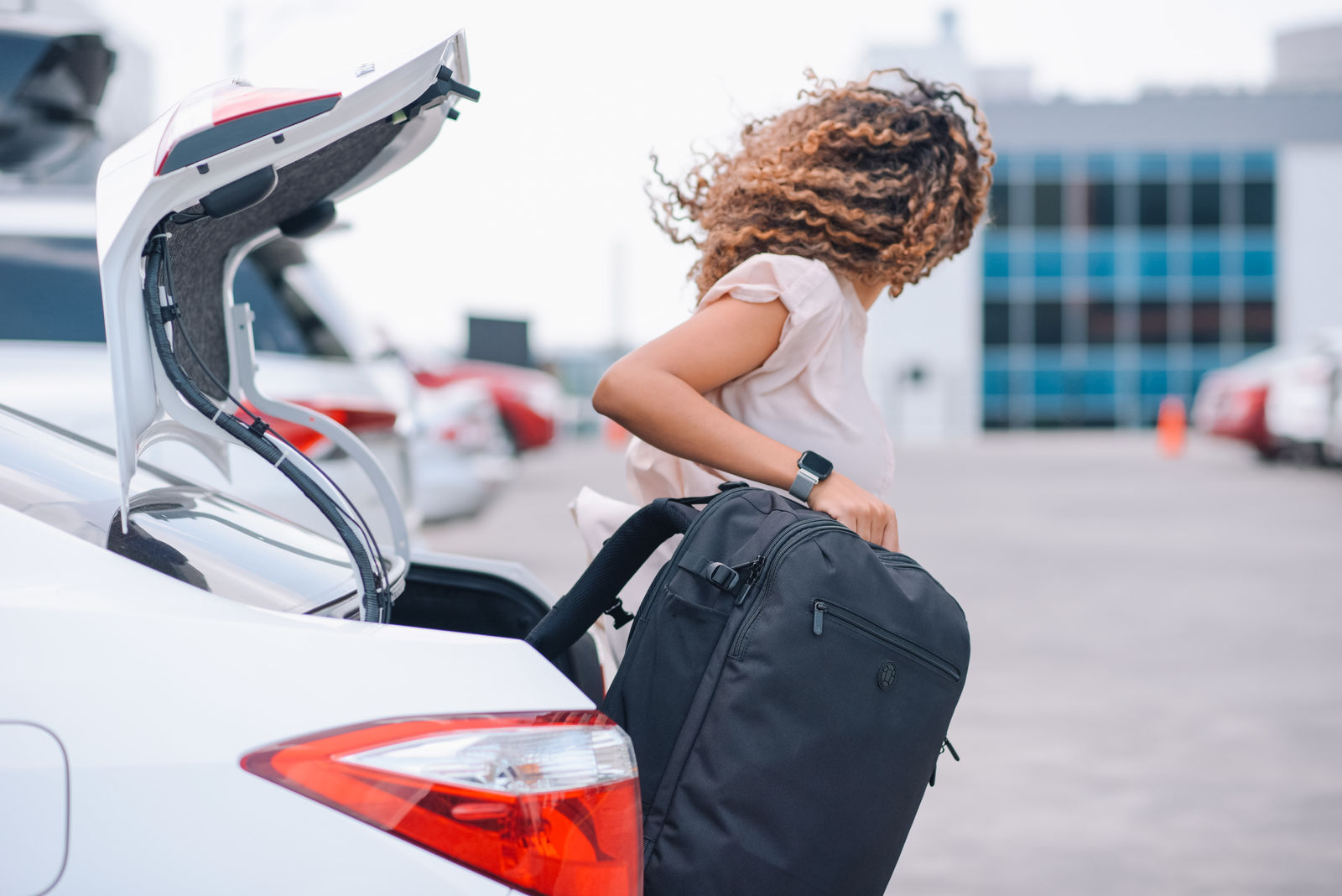 Removing backpack from trunk of car