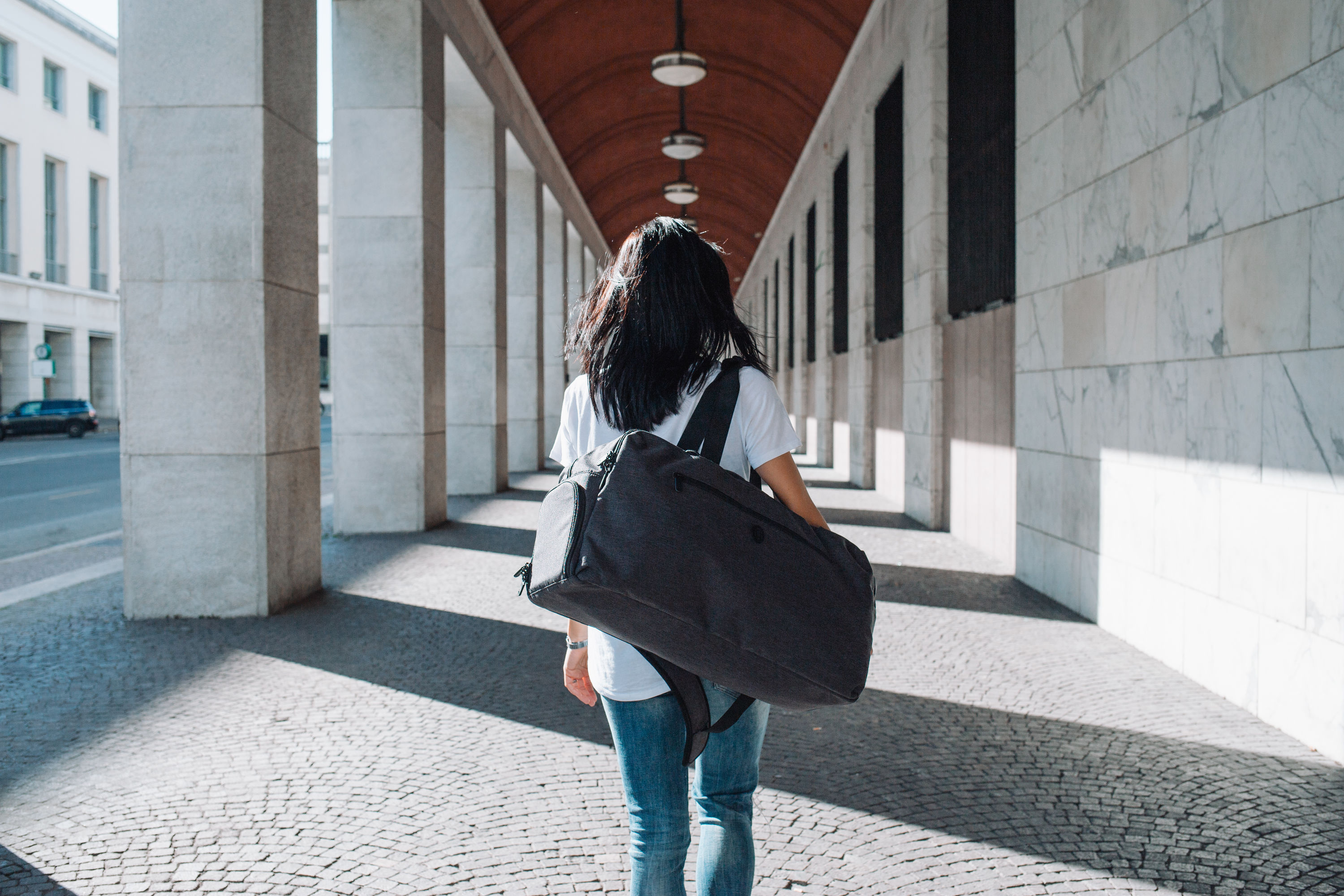 A woman carries a duffle bag in a portico.