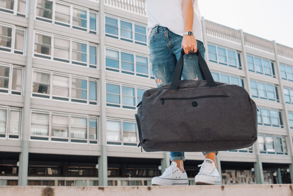 Holding a duffle bag with a building as the background