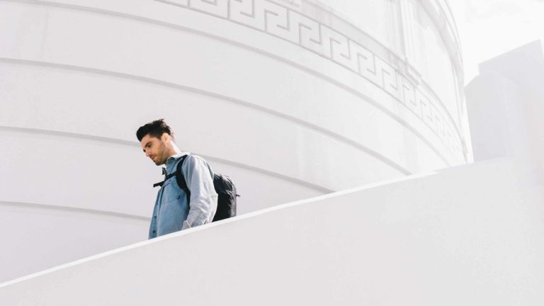 Man walking down stairs wearing backpack