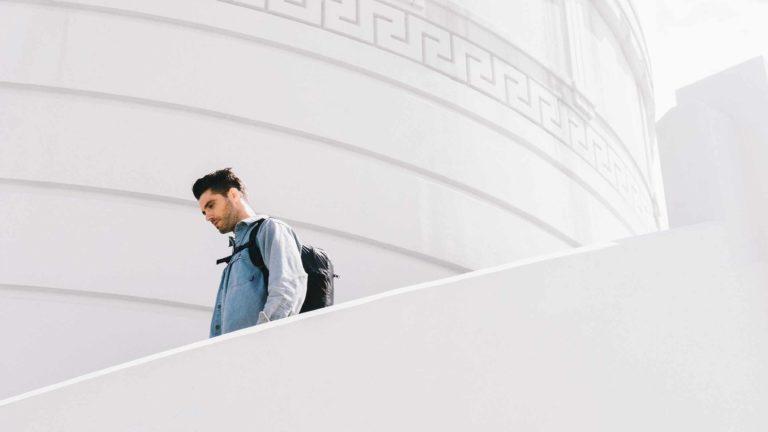 Man walking down stairs wearing backpack