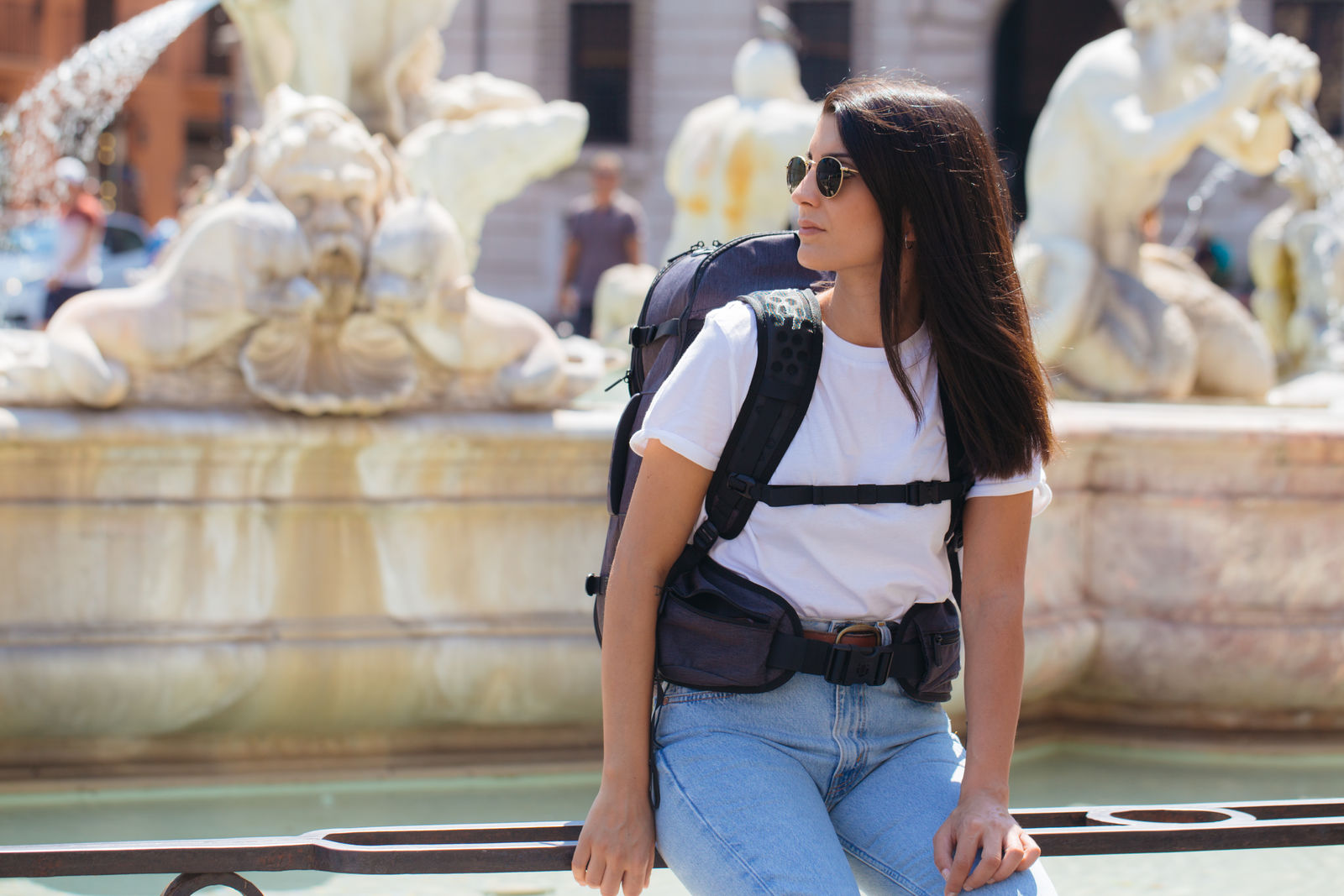 Woman sitting on fountain with backpack