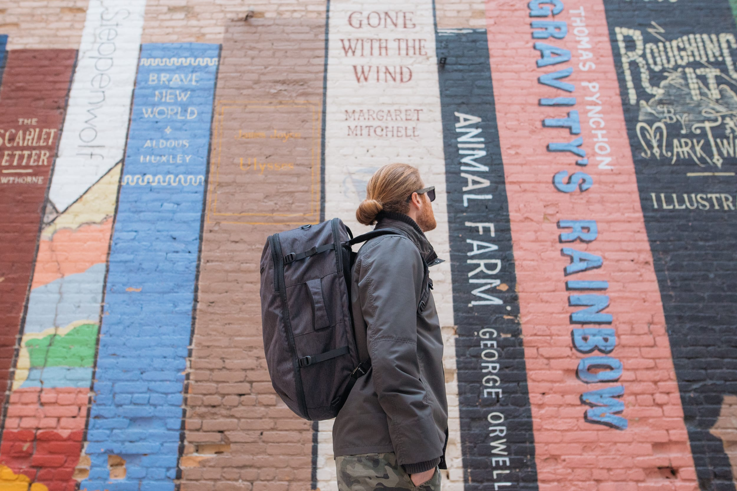 Man wearing travel jacket and backpack near an interesting wall