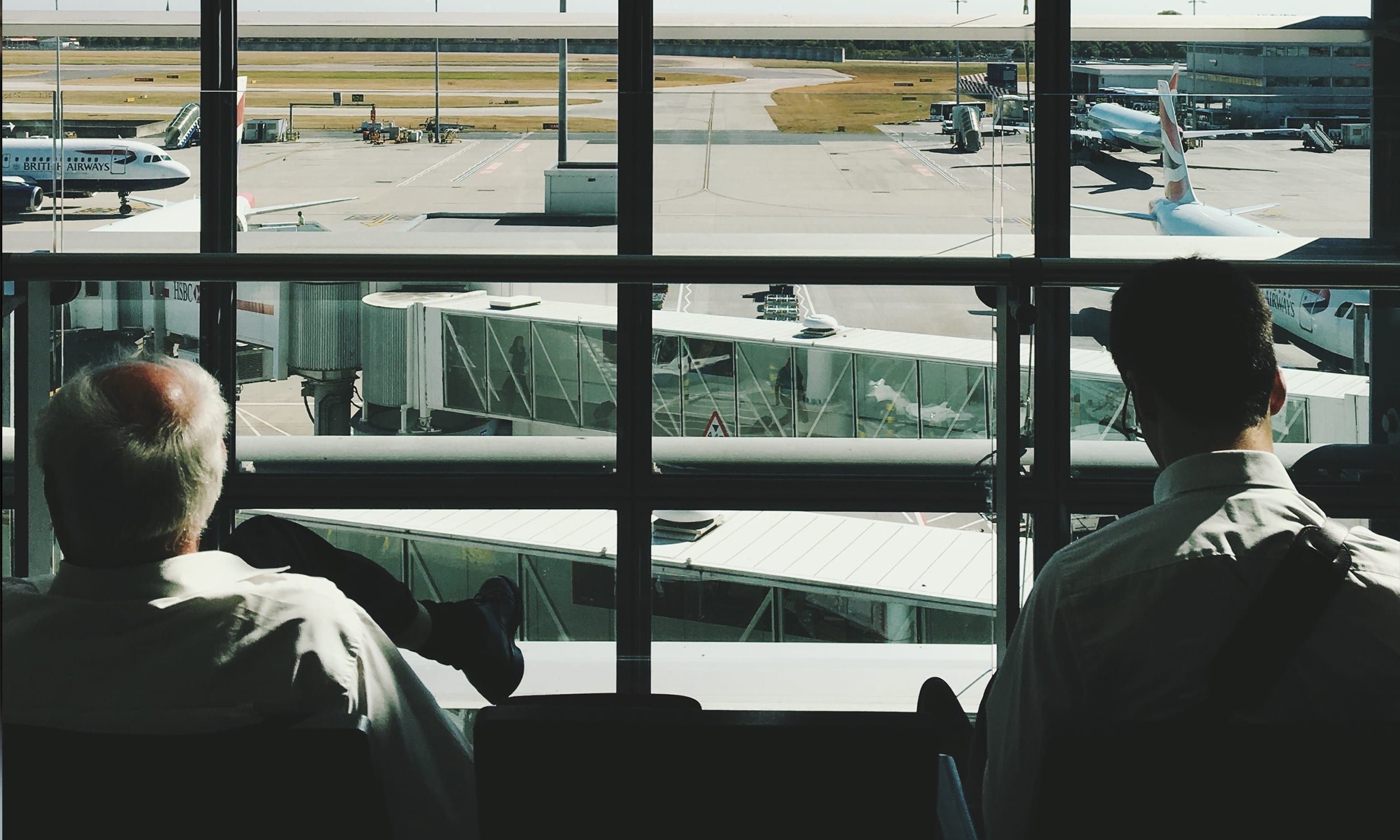 Men looking at airplanes from the airport lounge