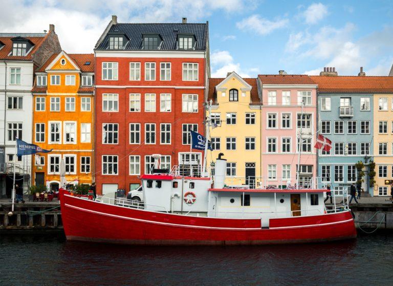 Boat passing colorful buildings in Copenhagen Denmark