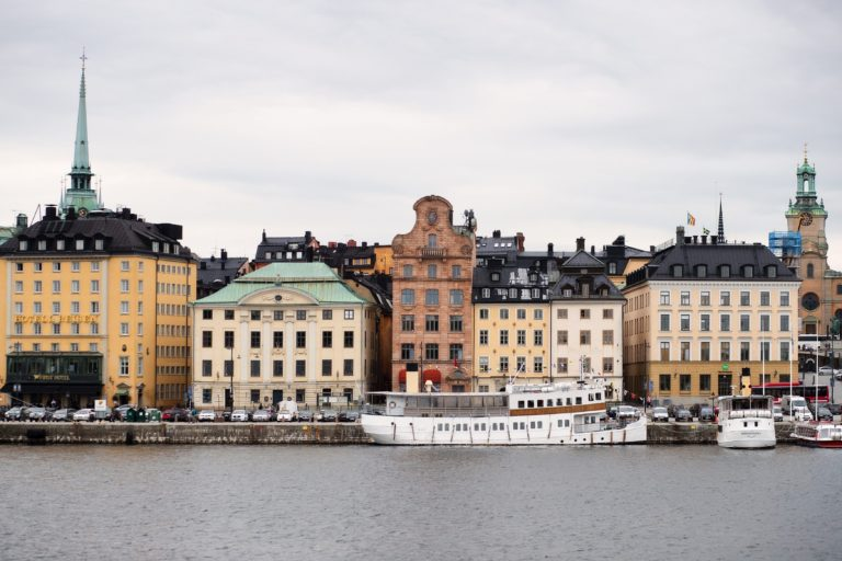 Boat passing by buildings somewhere in Scandinavia