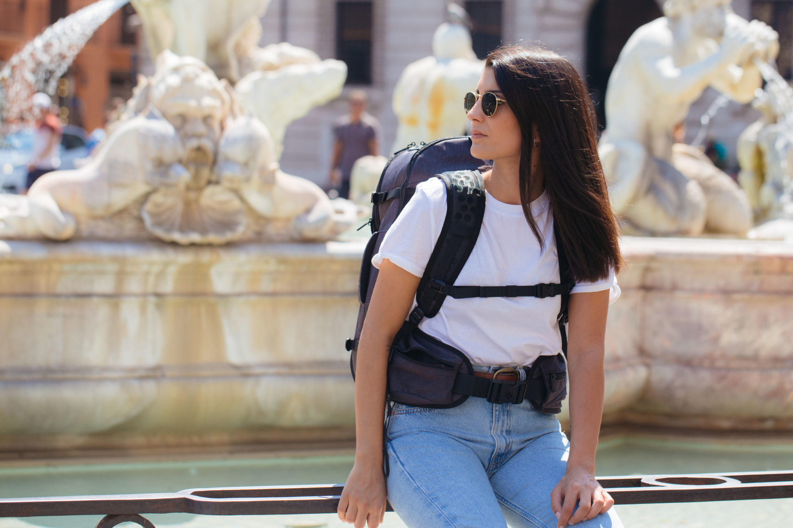 Woman visiting fountain in Rome wearing a backpack