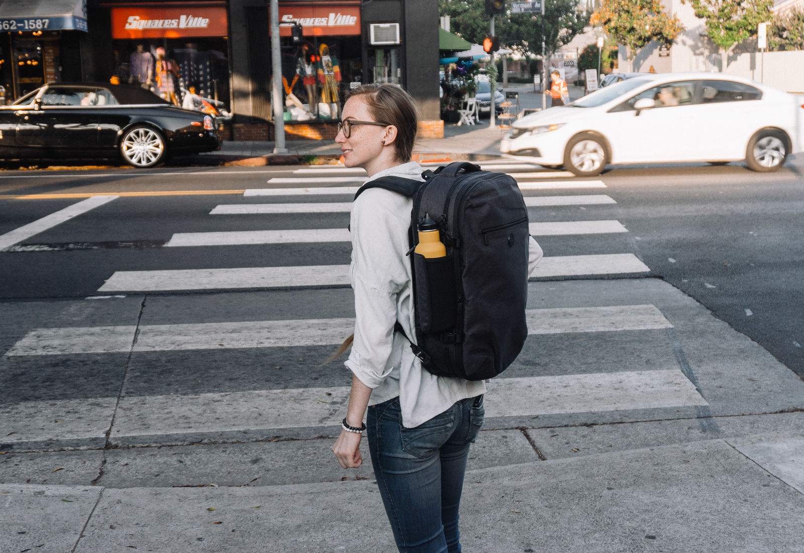 Woman carrying Tortuga backpack while crossing the street
